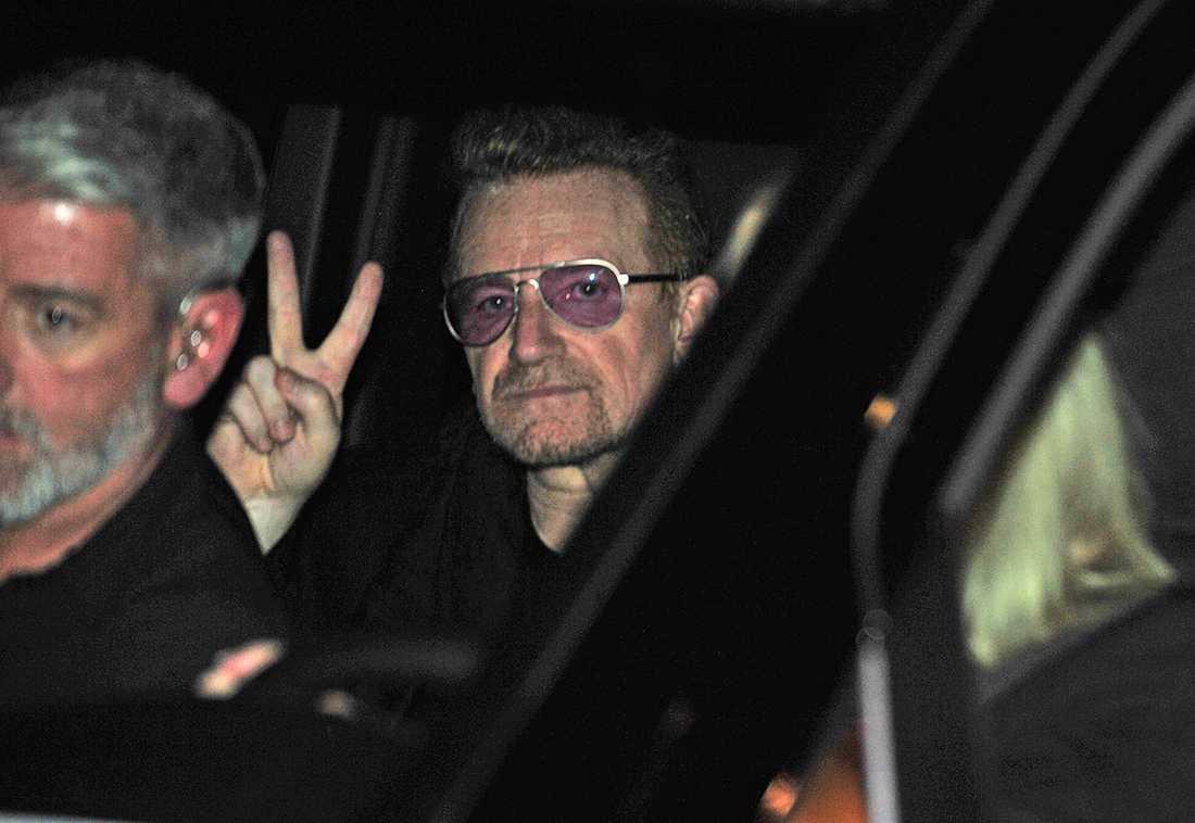 U2:s sångare Bono gör ett fredstecken från sin Mercedes-buss.