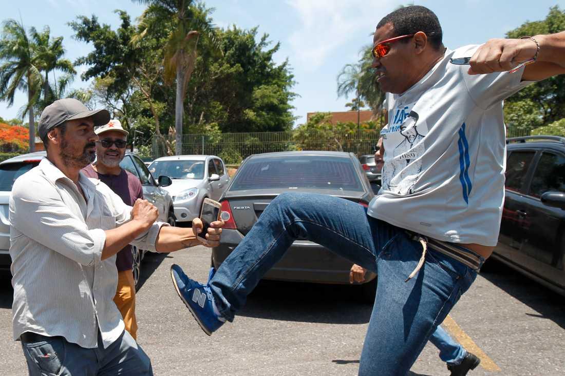 En Maduro-anhängare riktar en spark mot en meningsmotståndare utanför ambassaden.