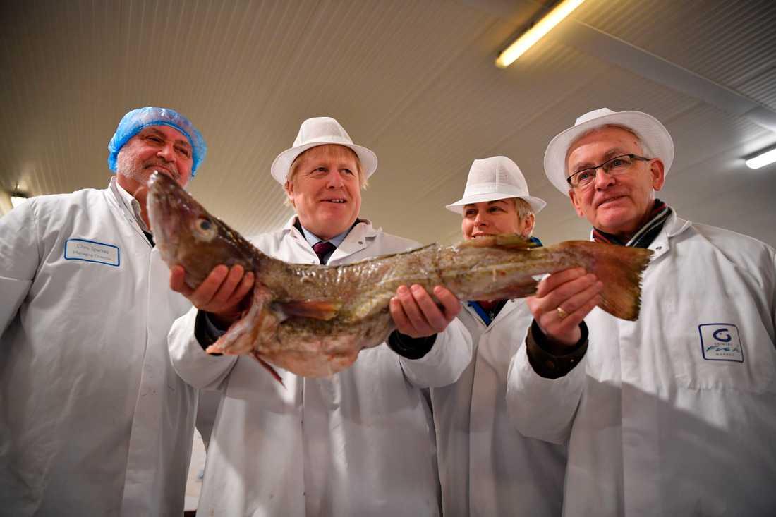 Boris Johnson håller upp en fisk.
