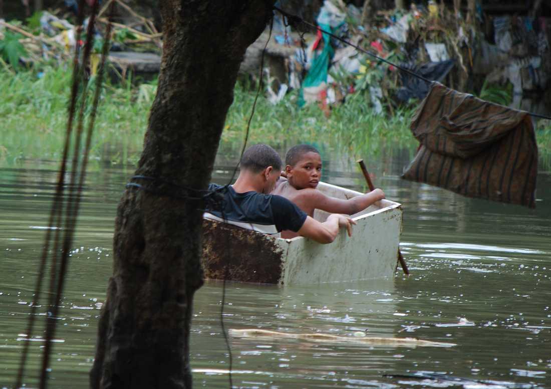 Ett par barn passar på att leka i översvämningsvattnet i Santo Domingo, Dominikanska Republiken.
