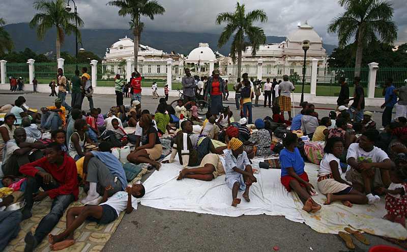 överlevande utanför palatset Port-au-Princes presidentpalats klövs i två delar i den kraftiga jordbävningen. Framför den kollapsade byggnaden samlades överlevande i går.