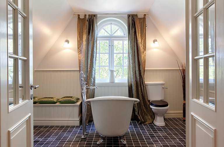 4.  Klassiskt badkar i ljusbadrum. Utsikt mot grönska i Djursholm.  Huset: Antal rum: 10 –  Boarea: 268 kvadratmeter – Pris: 22 000 000 kronor