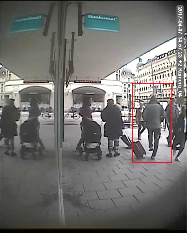 Akilov springer förbi Bankomaten, Vasagatan 11. Man kan tydligt se hålet i höger byxben.