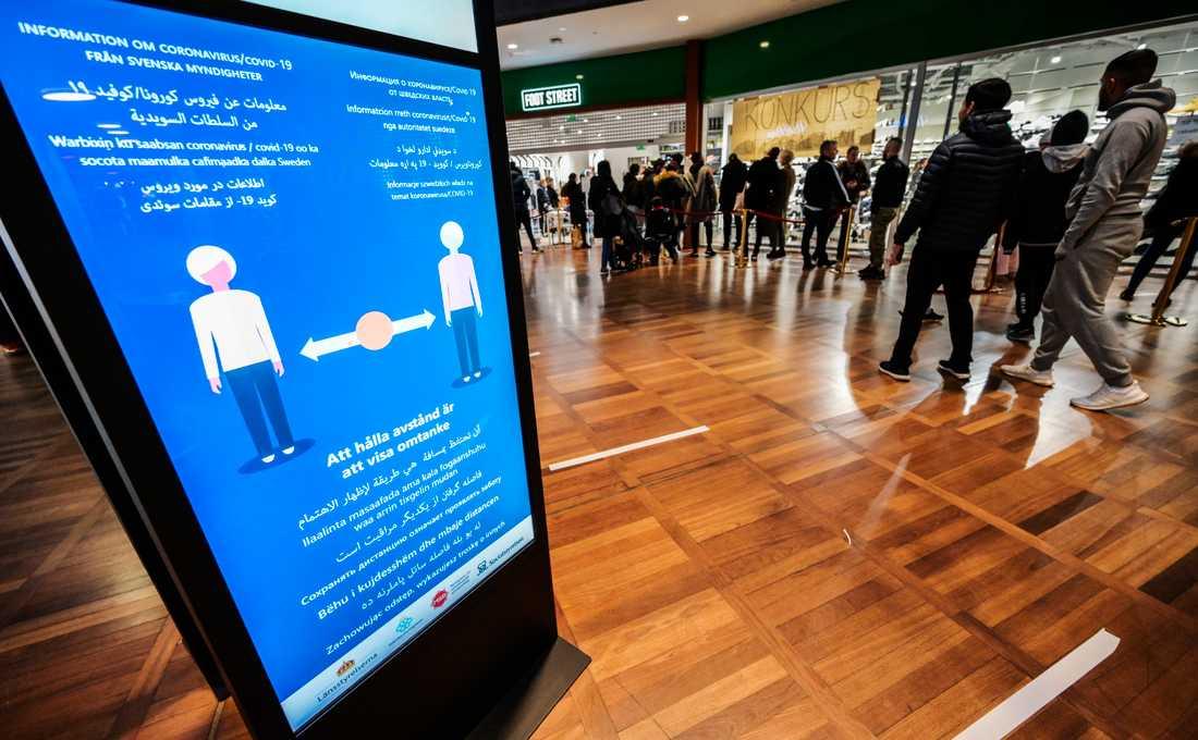 Coronainformation framför en kö till en butik i Malmö. Sedan pandemilagen trädde i kraft i söndags har få länsstyrelser satt i gång med kontroller. Arkivbild.
