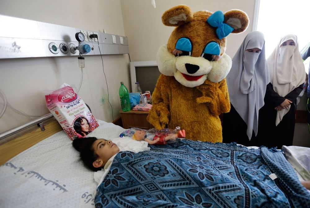 En palestinsk sjuåring som har blivit förlamad av granatsplitter får besök av en nalle när slutet på Ramadan firas på sjukhus i Gaza City. Sju av flickans familjemedlemmar dog i en attack mot stadsdelen Shajaiya.