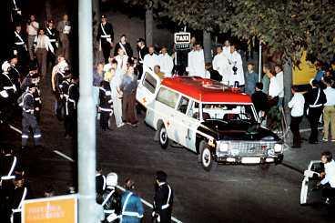 dramat är över Sent på kvällen den 28 augusti 1973 - efter nästan sex dygn - släpper polisen in gas i bankvalvet. Janne Olsson och Clark Olofsson ger upp. Här förs Olsson ut mellan två polismän.