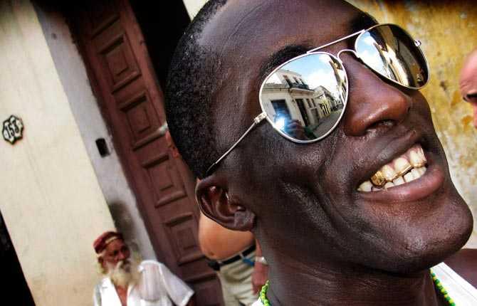 """""""Jag fick följa med Tata, i solglasögon, och Ernesto deras sista dag av tre i ceremonier som leder till att de får sitt beskyddande mano de orula. Det är en del i religionen Santería, som har sitt ursprung på Kuba."""""""