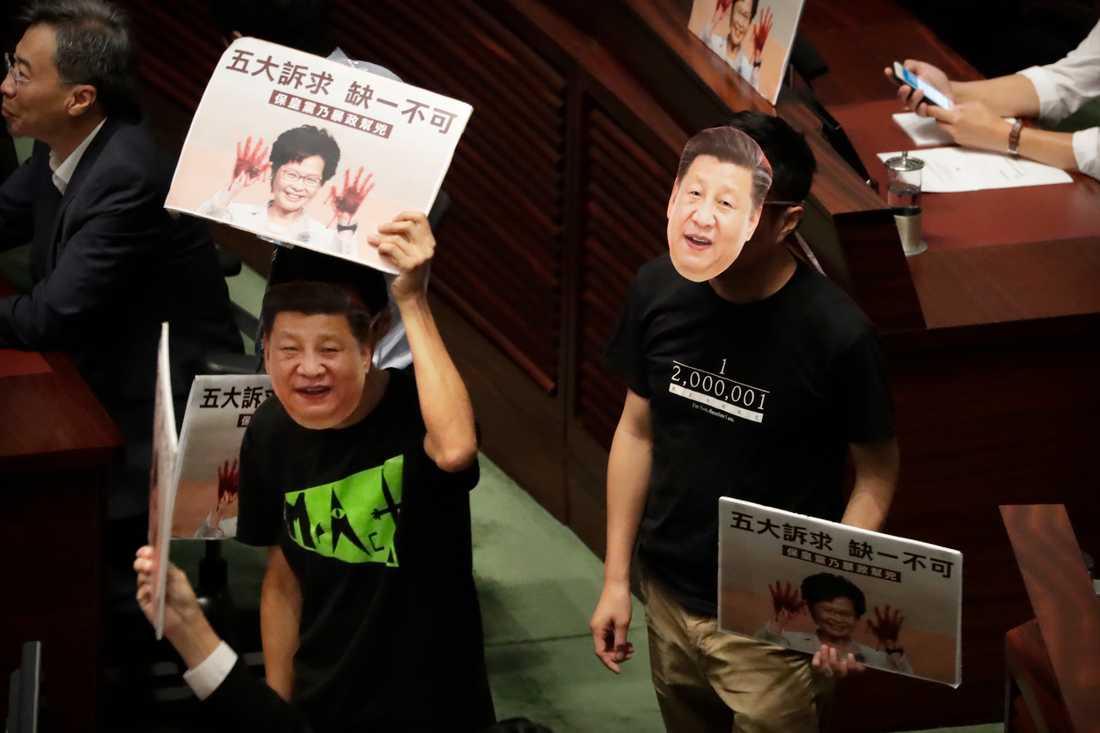 Demokrativänliga parlamentsledamöter bar masker föreställande Kinas president Xi Jinping när de avbröt Carrie Lams tal.