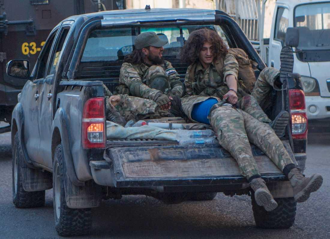 En sårad turkietstödd rebell evakueras av kamrater efter striderna mot kurdiska styrkor vid Tel Abyad, Syrien.