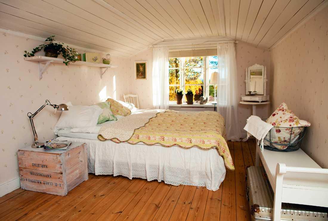 LANTLIGA DRÖMMAR. Mari och Johnnys sovrum andas sommar även om det är adventstider. Täcket/överkastet på sängen är köpt i butiken Systrarna Grene i Köpenhamn. Sänglampan och ljusringen är från Ikea. Lådan som är sängbord är ett fynd från loppis. Pigtittaren i hörnet har varit Maris mormors.
