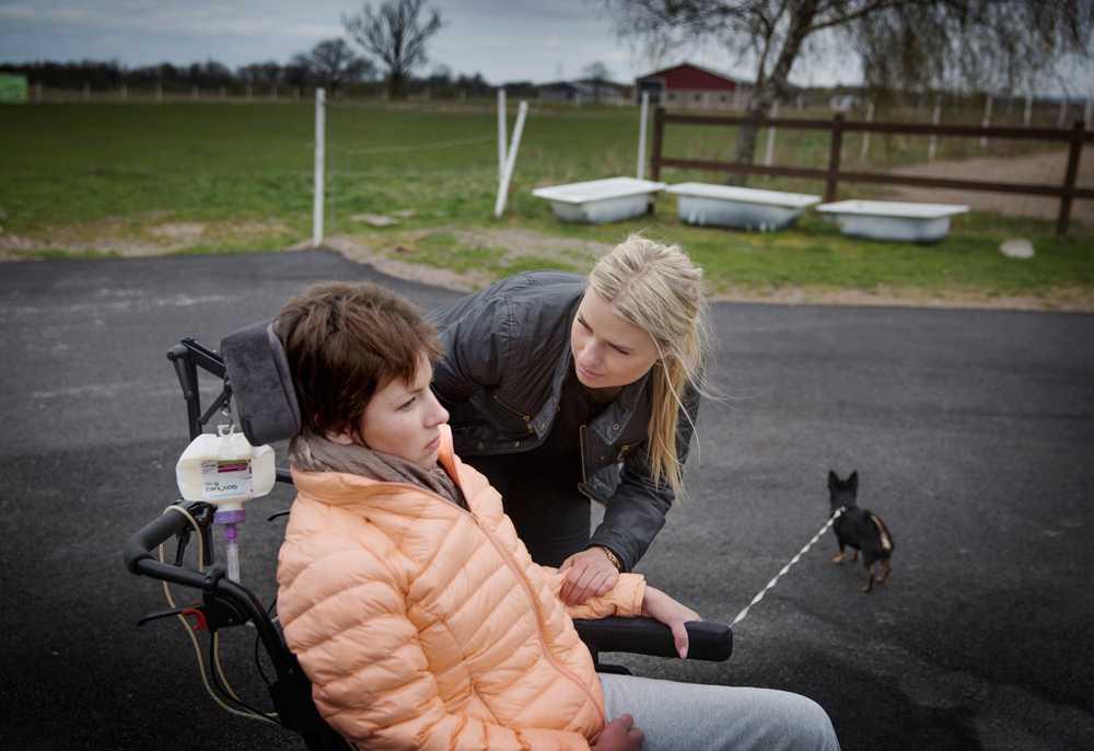 Nicole på gården i Mörarp där hon bor med sina föräldrar. Här med assistenten Emma. Maj 2015.