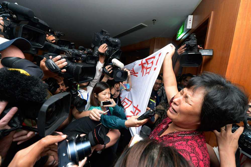 Sörjande anhöriga håller upp en banderoll där de kritiserar malaysiska mybdigheter för att inte göra tillräckligt för att hitta MH370.