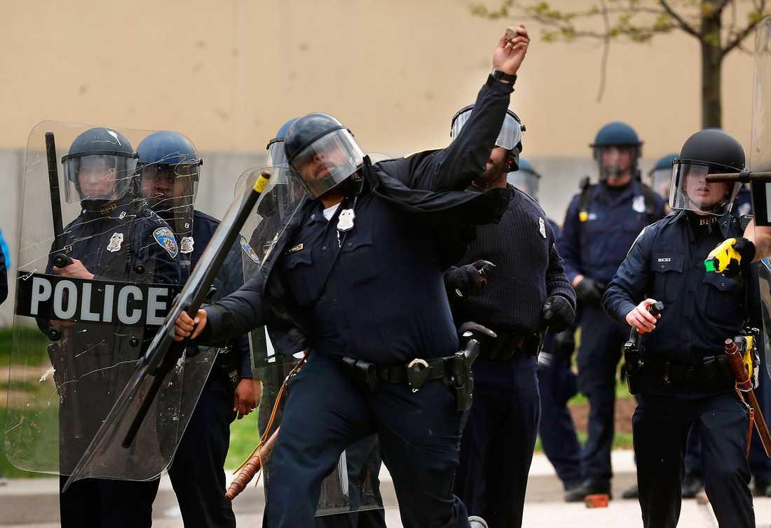 En polis kastar sten.