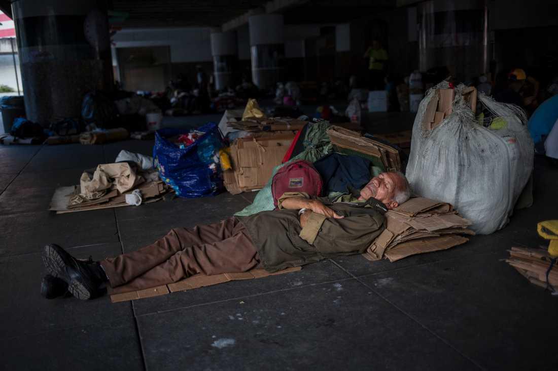 En man sover utanför Venezuelas centralbank i Caracas i protest mot att oljearbetare inte fått sina pensioner utbetalda. Bild från den 16 juli.