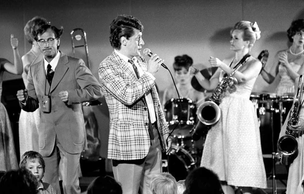 """1988 Lasse Brandeby som Kurt Olsson i tv-serien """"Fådda blommor"""", tillsammans med sidekicken Hans Wiktorsson och den berömda damorkestern."""