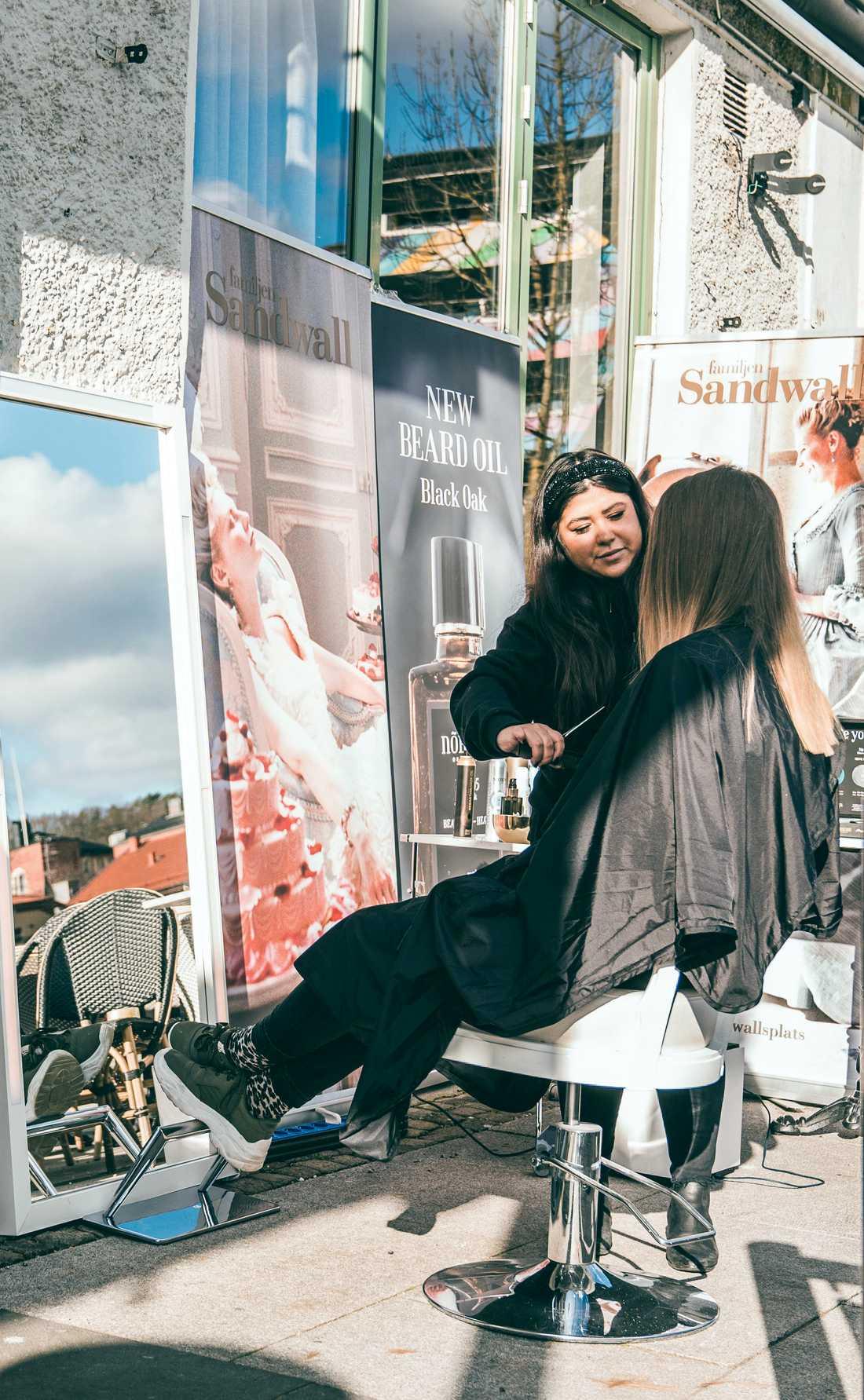 Utanför salongen finns en uteservering som den här våren lånar ut en liten del av sin serveringsyta. Några restaurangbord har plockats bort för att ge plats åt frisörstol, speglar, fönar och lite hårprodukter.