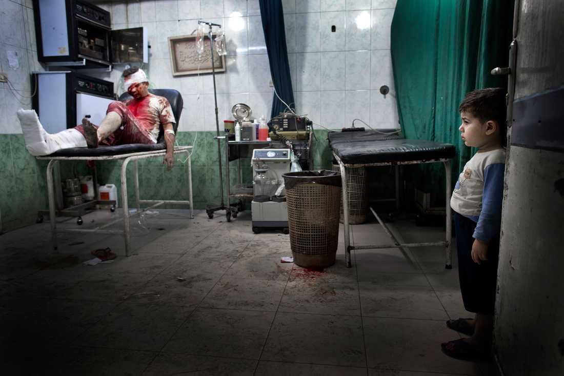 En liten pojke tittar på en skadad man i en av sjukhusets operationssalar.