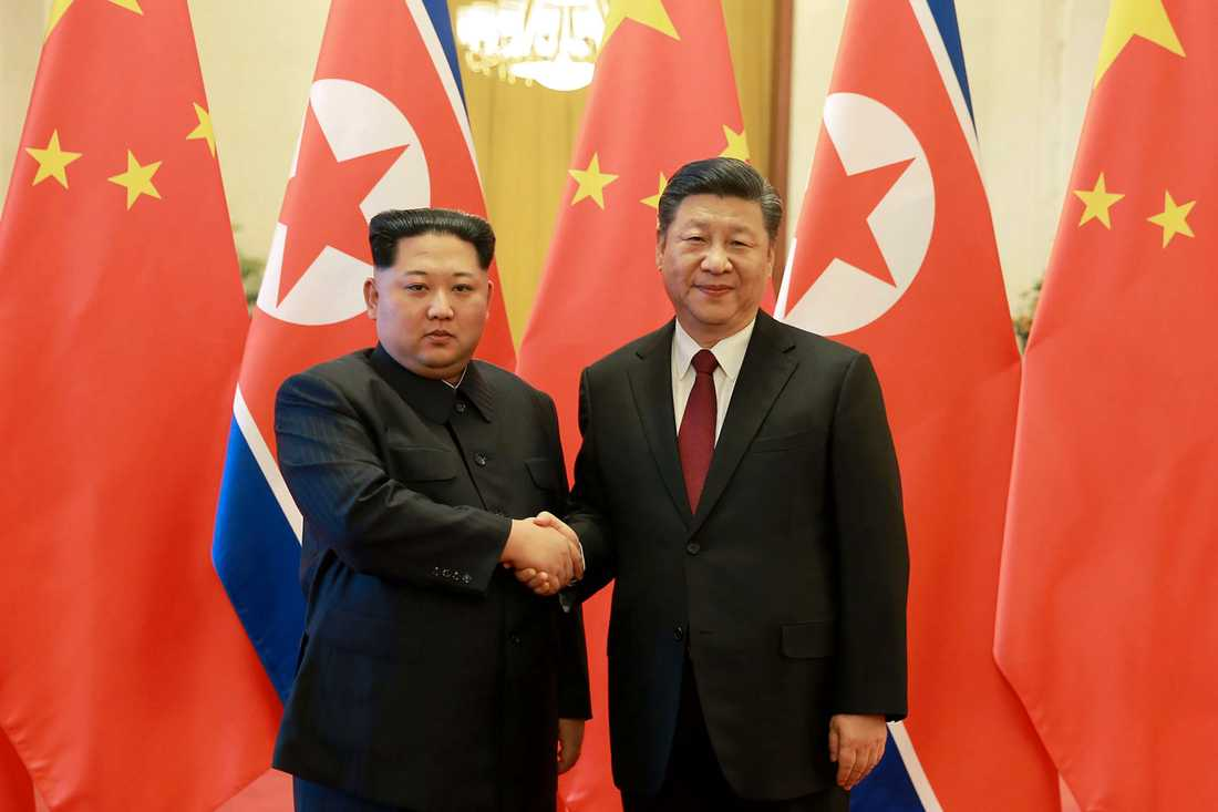 Kim Jong-un skakar hand med Kinas Xi Jinping .