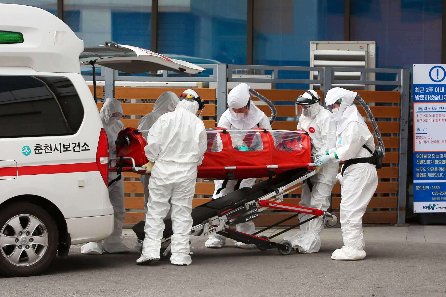 Ambulansvårdare transporterar en coronasmittad patient till ett sjukhus i Sydkorea.