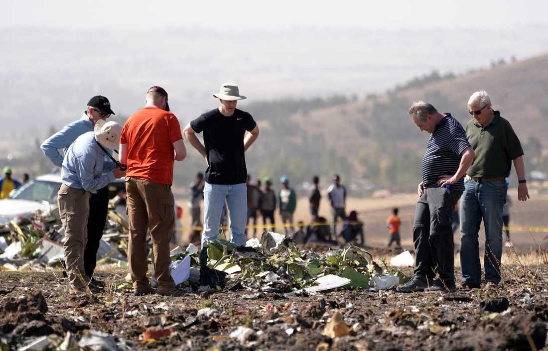 Personer inspekterar delar av flygplansvraket.