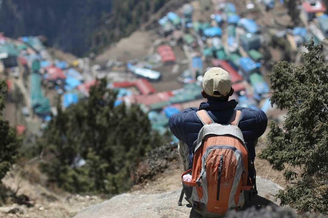 En man blickar ut över sin hemby Namche i Everest-området.
