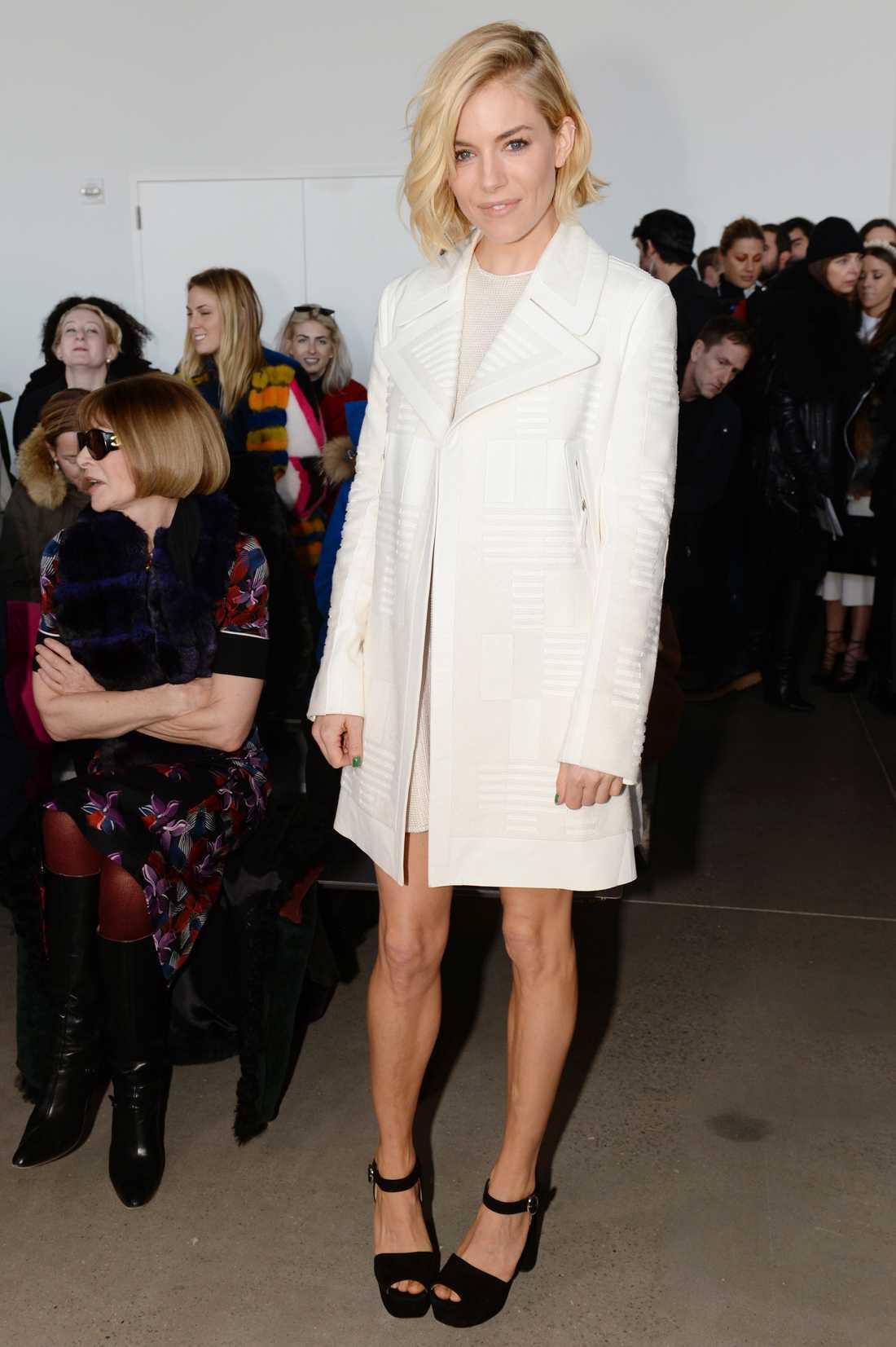 Sienna Miller Sienna matchar sin krispigt vita kappa med 90-talsinpirerade skor. Gillar du också looken? Spana in shoppingtipset nedan.