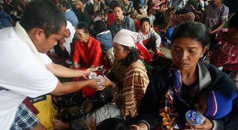 Byborna som bor i sluttningen under vulkanen får mat i ett tillfälligt upprättat skyddsläger i Karo.