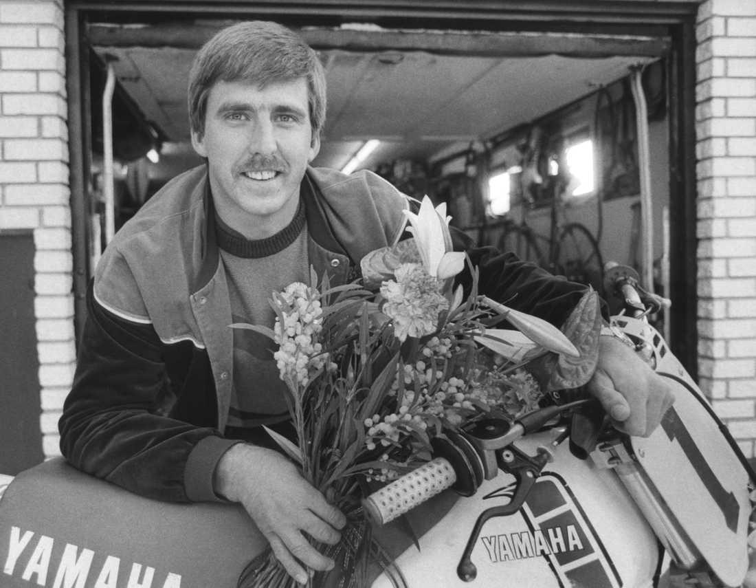 Lyckligt leende med segerbukett lutad mot motorcykeln, 1983.