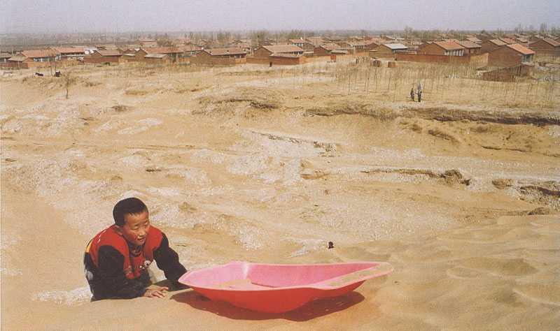 KINA 8-årige Dang Guo Qing leker bland sanddynorna som invaderat byn där hans mor och far brukade föda upp boskap – de gav upp och begav sig till Beijing i hopp om att få jobb. Dang Guo Qing tas om hand av sin farfar.