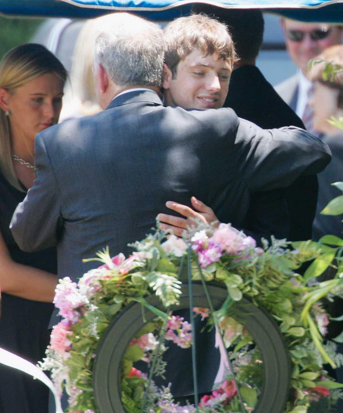 Burke Ramsey kramar om sin pappa John under en ceremoni 2006 vid gravplatsen för mamma Patsy och lillasyster JonBenét.