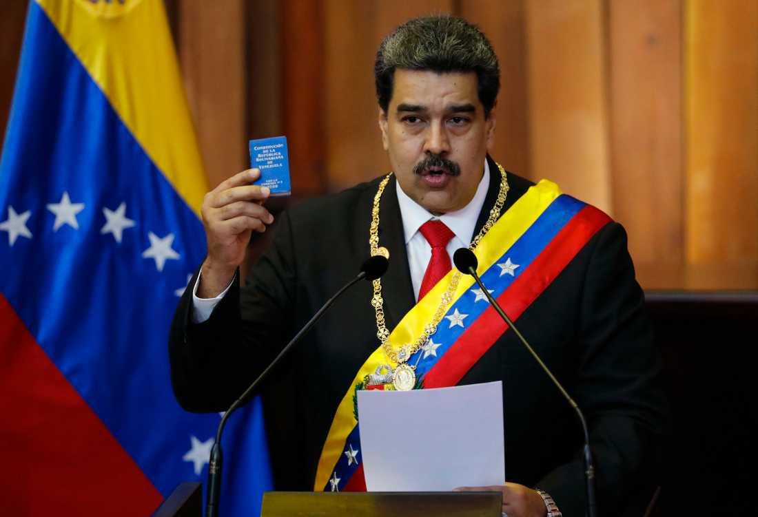 Venezuelas president Nicolas Maduro håller upp en liten kopia av landets konstitution när han svärs in som president.