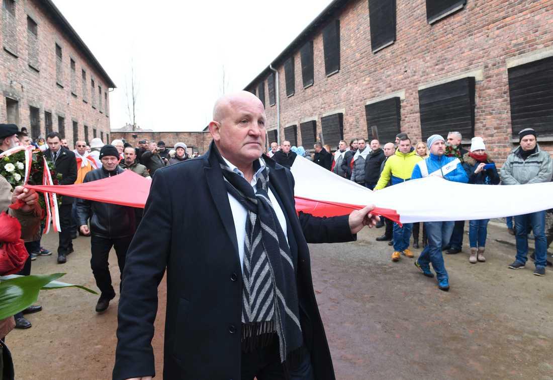 Polska högerextremister bär en stor polsk flagga genom Auschwitz.