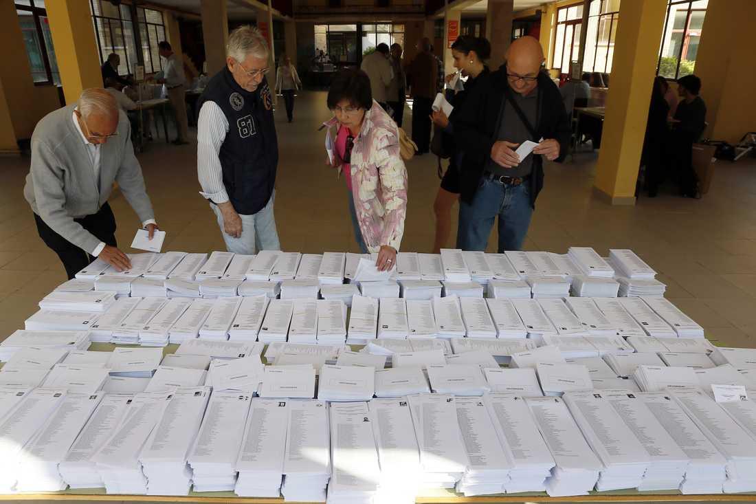 Spanska väljare väljer bland valsedlar i en vallokal i Madrid.