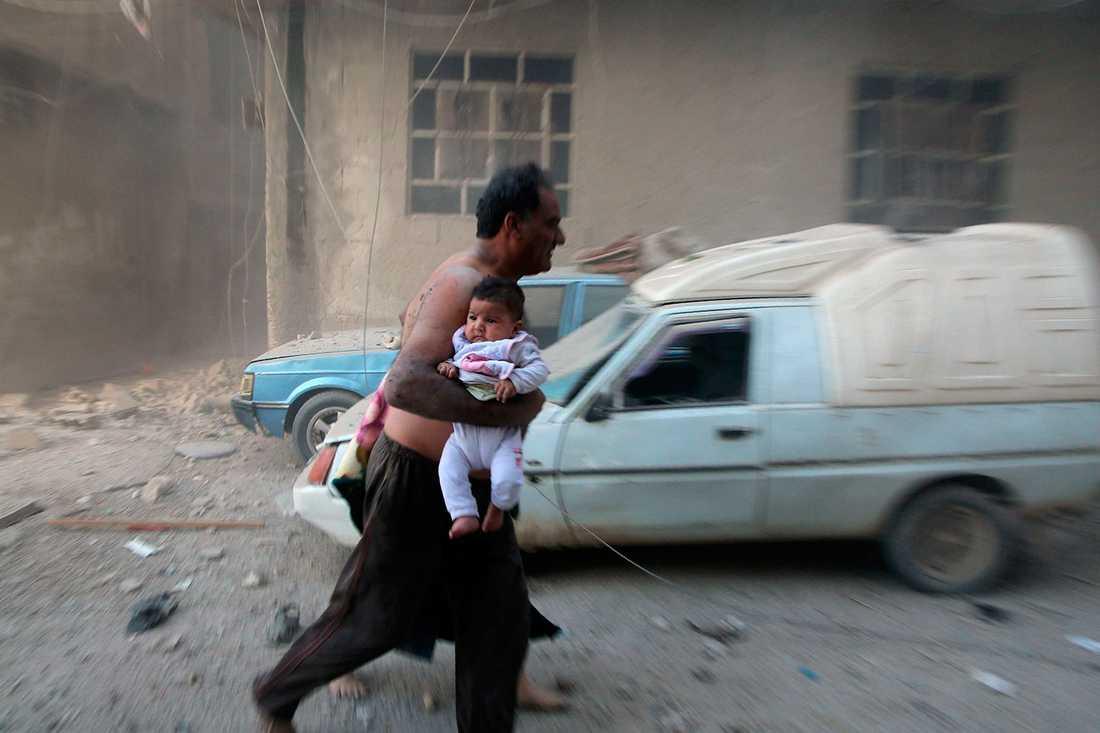 En man flyr i bara byxorna med ett litet barn under armen i Kafr Batna strax efter att bomberna slagit ner.