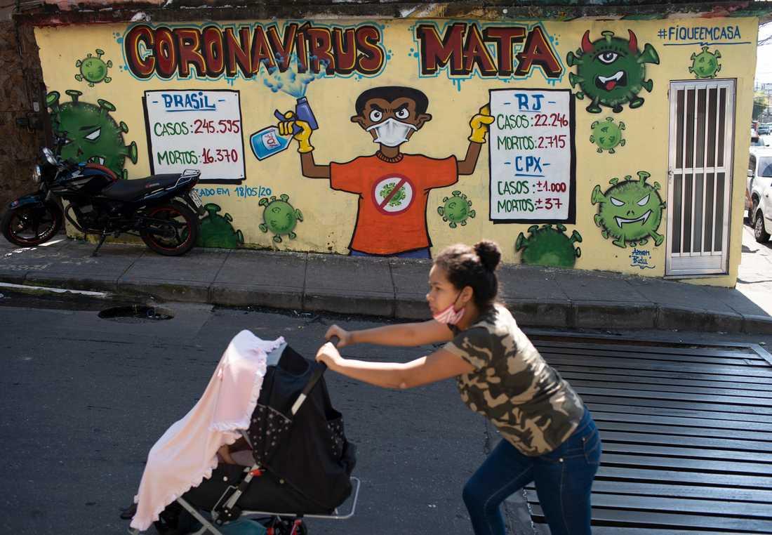 """En muralmålning med texten """"coronavirus dödar"""" syns på en vägg i kåkstaden Alemao i Rio de Janeiro. En brasiliansk domstol har nu satt stopp för polisens räder i kåkstäderna fram till dess att pandemin är över."""