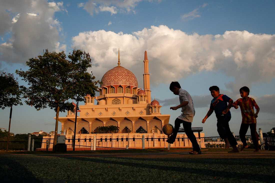 Malaysiska barn framför Putramoskén i Putrajaya Malaysia.