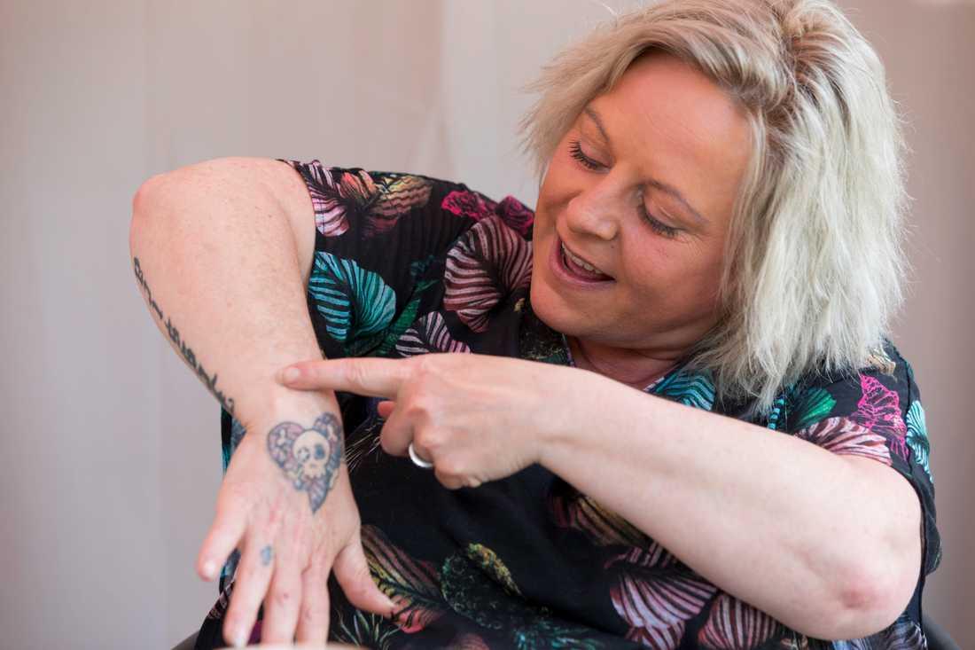 Bakom tatueringen göms ett stort ärr. Där satte exmannen en täljyxa i handen på henne.