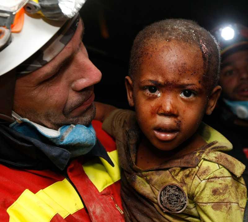 En spansk hjälparbetare bär undan tvåårige Redjeson Hausteen Claude efter att han räddats från sitt kollapsade hem. Pojken hade varit fast i 48 timmar.