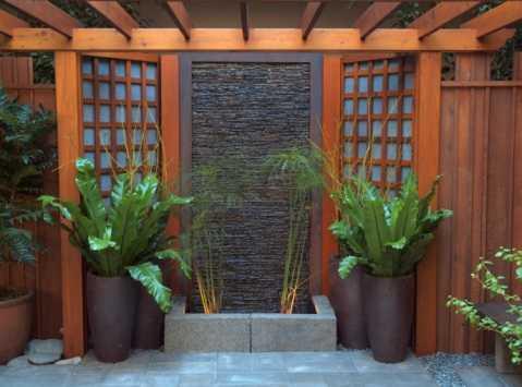 Pergolan kan varieras i det oändliga. Här ett japanisnpirerat bygge med fontänvägg i svart räfflad sten och träkonstruktion i ädelträ. Tjusigt.