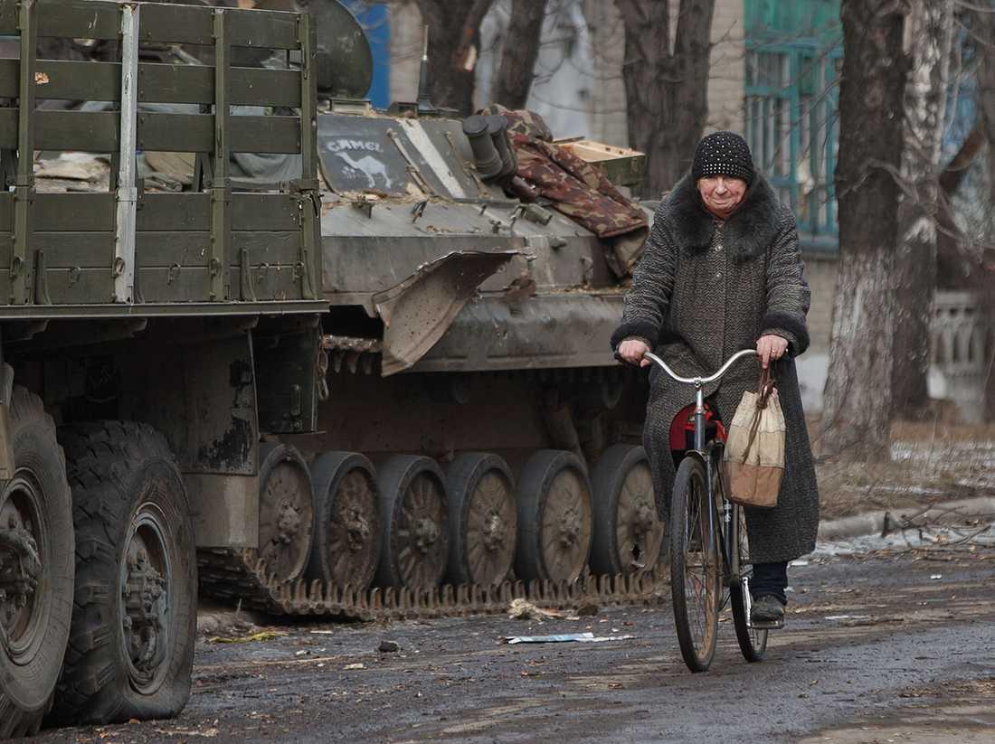En kvinna cyklar förbi militärfordon i Debaltseve.