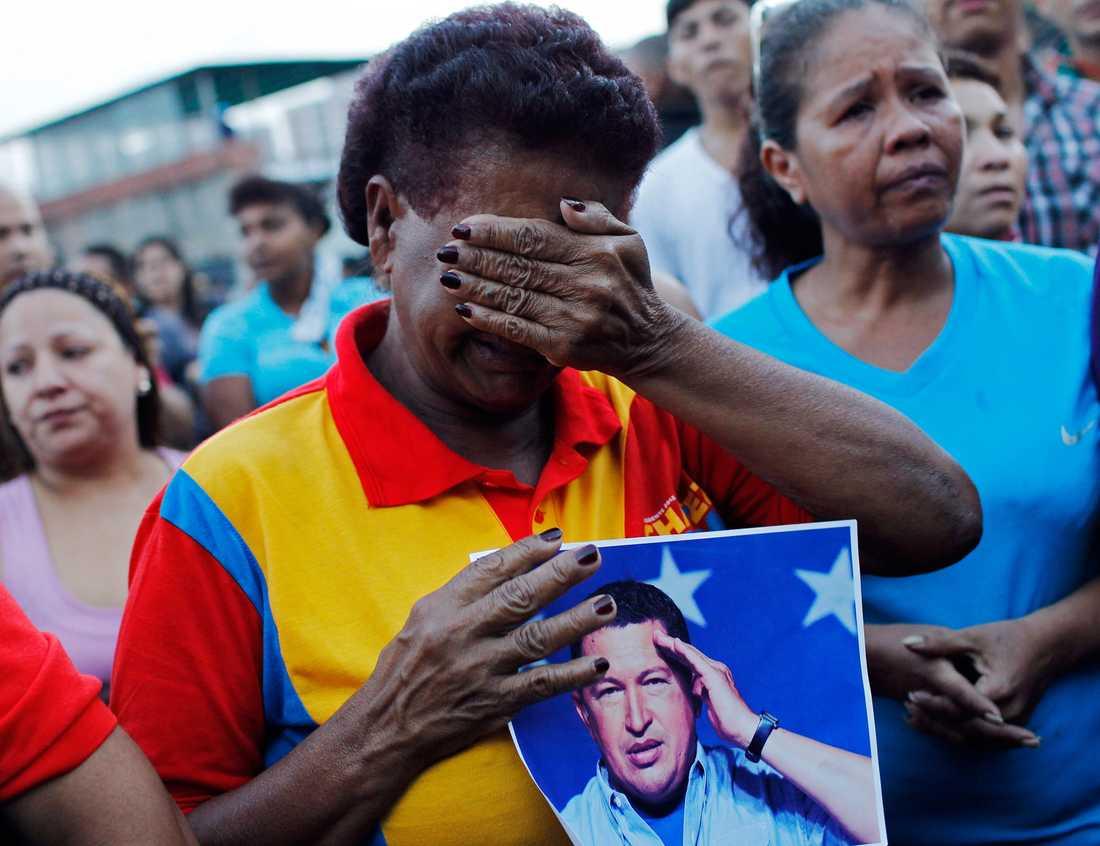 En ledsen kvinna med ett porträtt av Chavez.