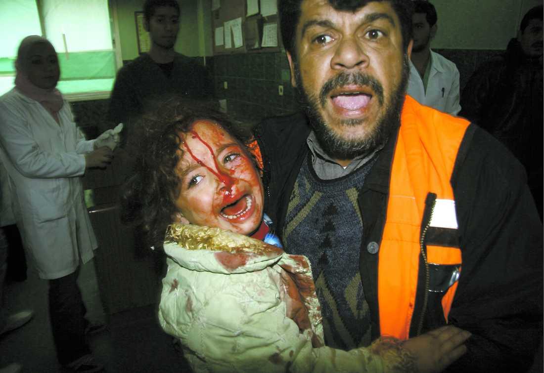 BARNEN HÅRT DRABBADE Den lilla flickan skriker av skräck och smärta när hon tas omhand av en sköterska på Shifa-sjukhuset efter en israelisk raketattack mot Gaza City.
