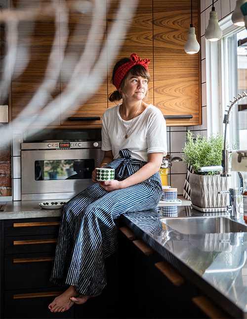 Sofia, eller Fröken röd som hon kallas, i sitt nyrenoverade kök, med sitt älsklingsporslin, Berså av Stig Lindberg. Lamporna i fönstret kommer från Tove Adman.