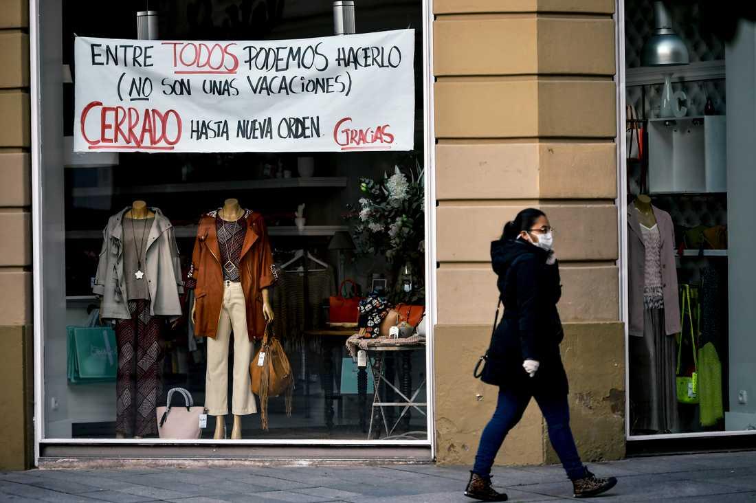 En kvinna med skyddsmask vid en stängd butik i spanska Pamplona.