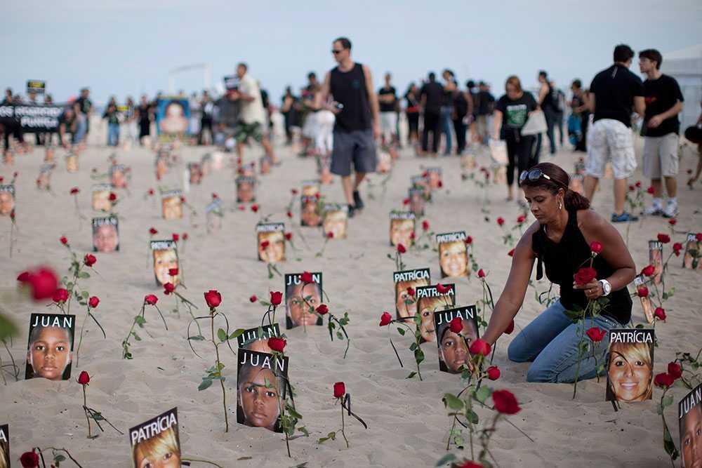 En kvinna sätter en blomma vid fotografiet av Juan Moraes på en strand i Rio de Janeiro. 11-åriga Moraes dödades under en polisinsats 2011 och på fredagen dömdes fyra poliser till över 30 års fängelse för att ha dödad pojken.