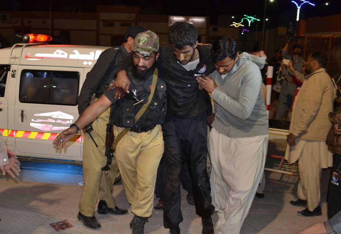Pakistansk volontär och en polis hjälper en skadad person till en sjukhus efter attentatet i Quetta.