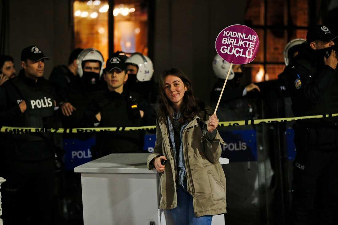 """En demonstrant i Istanbul står med ett plakat där det står """"Kvinnor är starka tillsammans"""". Arkivbild."""
