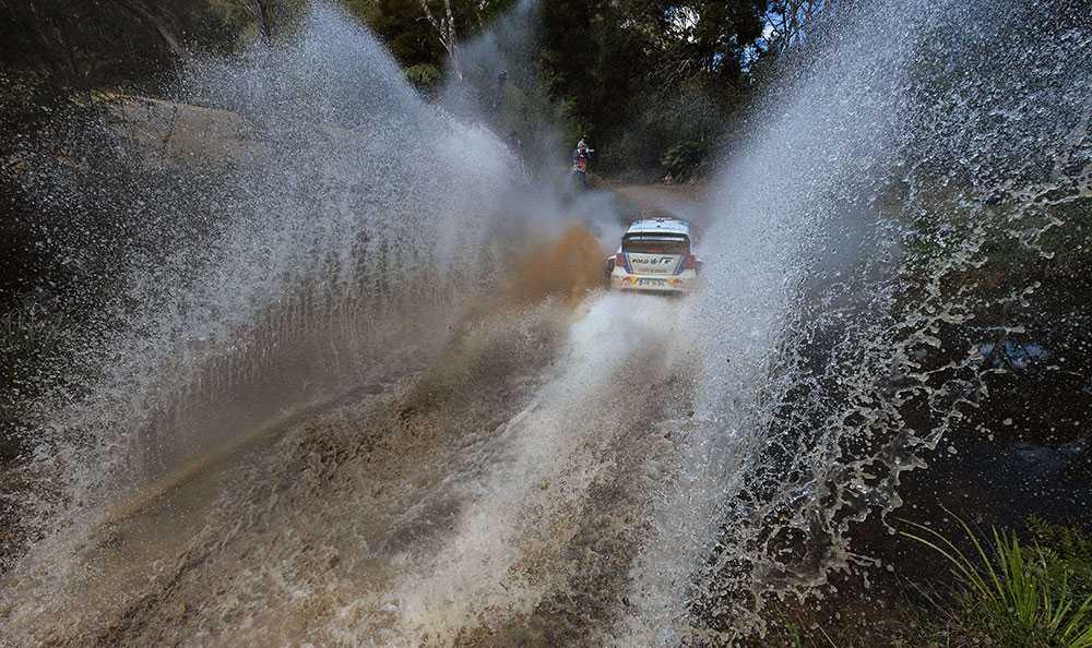 Fransmannen Sebastien Ogier kör genom ett vattenhinder på väg mot seger i det australiska rallyt.