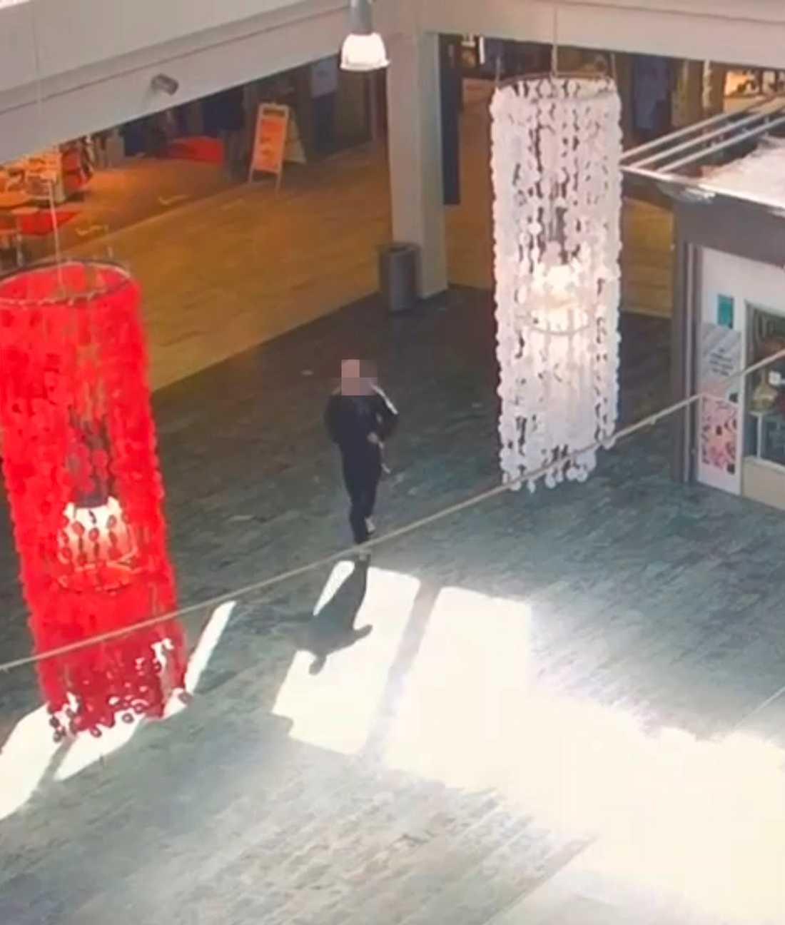 Mannen syns vandra genom ett köpcentrum på övervakningsfilmer.