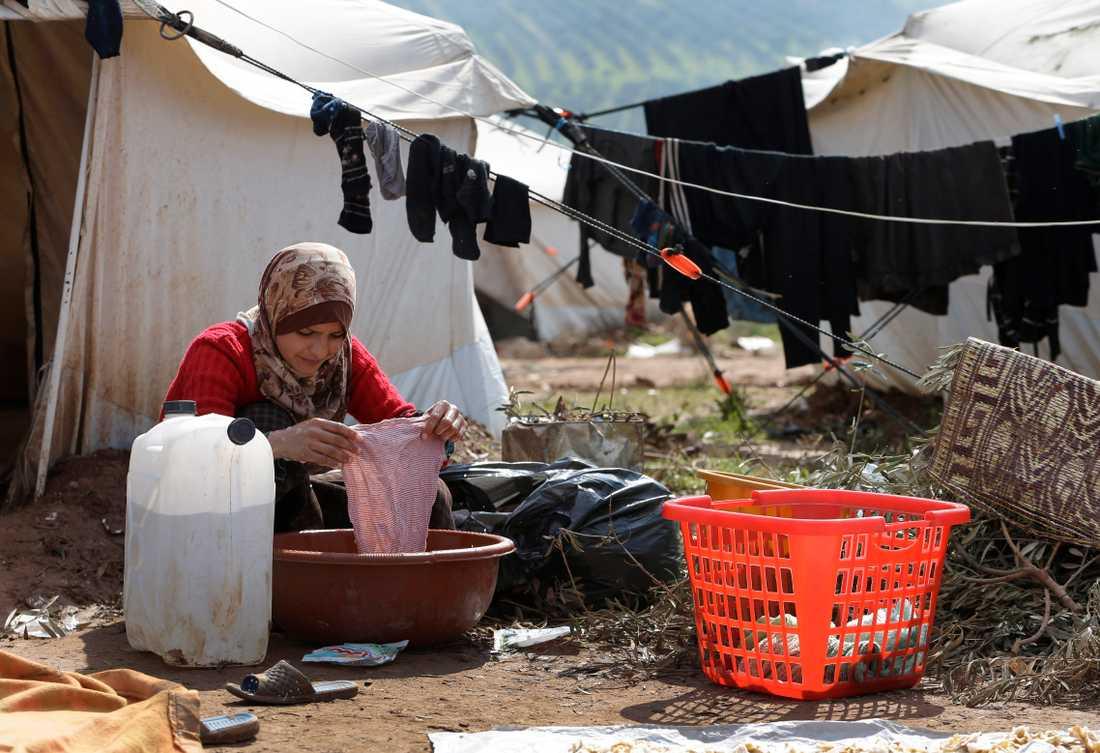 En kvinna tvättar kläder utanför sitt tält i ett flyktingläger i staden Atmeh i norra Syrien. Om coronaviruset får fäste i området vore det förödande, varnar hjälporganisationer. Arkivbild.